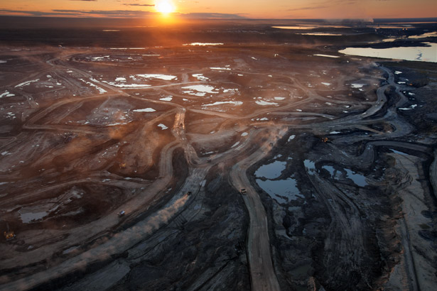 Dust hangs in the sunset sky above the Suncor Millennium mine, an open-pit north of Fort McMurray, Alberta. Canada's oil sands are layers of sticky, tarlike bitumen mixed with sand, clay, and water. Around a hundred feet of soil must be stripped off to reach many deposits. Photo: Peter Essick, National Geographic