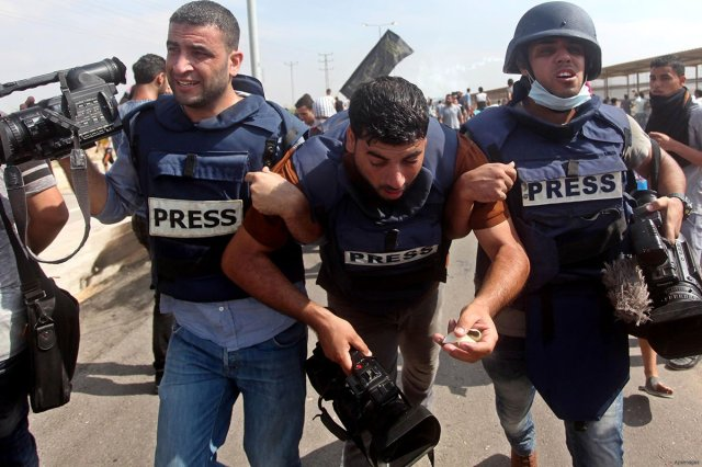 Palestinian journalists help their injure colleague get to safety after being attacked by Israeli soldiers near the Erez Crossing on October 13th 2015 Photo:Middle East Monitor